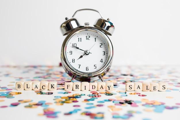 Inscripción de ventas de viernes negro en cubos blancos con reloj. Foto gratis