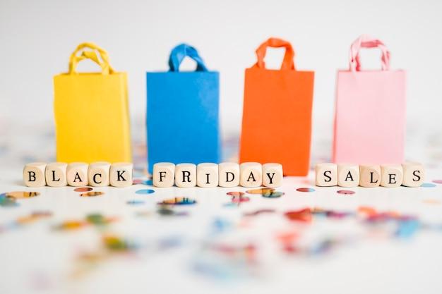Inscripción de ventas de viernes negro en cubos con coloridas bolsas de compras. Foto gratis