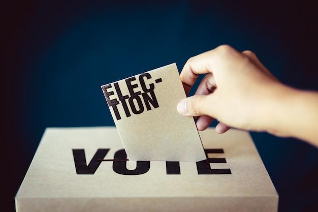 Inserción de tarjeta electoral en casilla de votación, concepto de democracia, tono retro Foto Premium