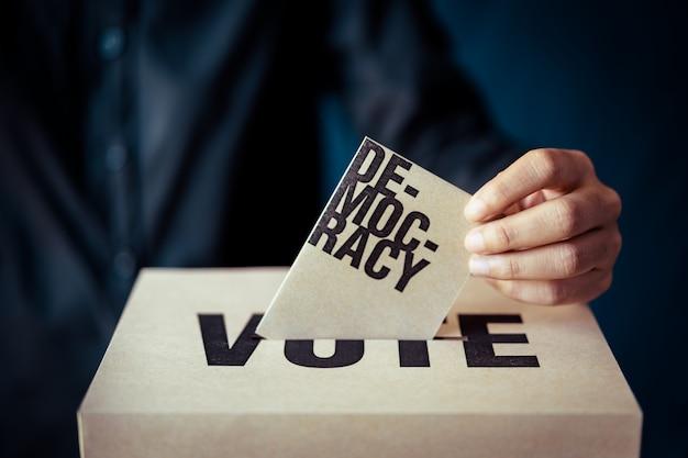 Inserto de papel marrón en la casilla de votación, concepto de democracia, tono retro Foto Premium