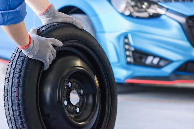 Inspección del automóvil del hombre asiático medir la cantidad de llantas de goma infladas automóvil. primer mano sujetando el neumático y el automóvil azul para la medición de la presión de los neumáticos para automoción, automóvil Foto Premium