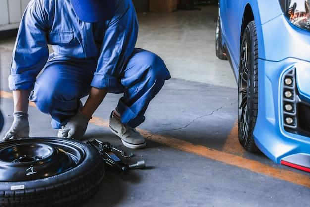 Inspección del automóvil del hombre asiático medir la cantidad de neumáticos de goma inflados del automóvil. Foto Premium