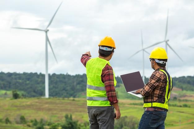 La inspección y el progreso de dos ingenieros de molinos de viento verifican la turbina eólica en el sitio de construcción. Foto Premium