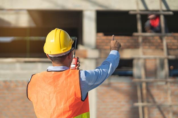 Inspector asiático que verifica la estructura de la nueva propiedad y toma nota en el portapapeles para revisar y arreglar la casa antes de venderla al cliente Foto Premium