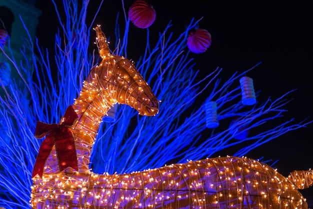 Instalación de reno decorado iluminado con luces durante la navidad Foto gratis