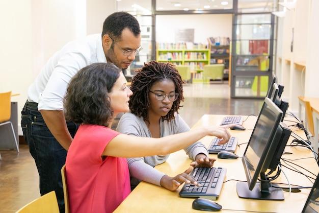 Instructor ayudando a estudiantes en clase de computación Foto gratis