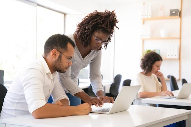Instructor ayudando a pasante a comenzar a trabajar en la computadora portátil Foto gratis