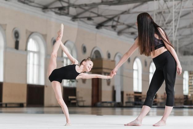 Instructor de ballet ayudando a la joven bailarina con posición de ballet Foto gratis