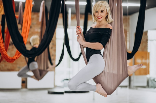 Instructora femenina de yoga con mosca en el gimnasio Foto gratis