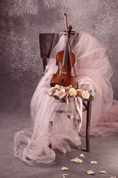 Instrumento de violín vintage con rosas y zapatillas de ballet Foto gratis