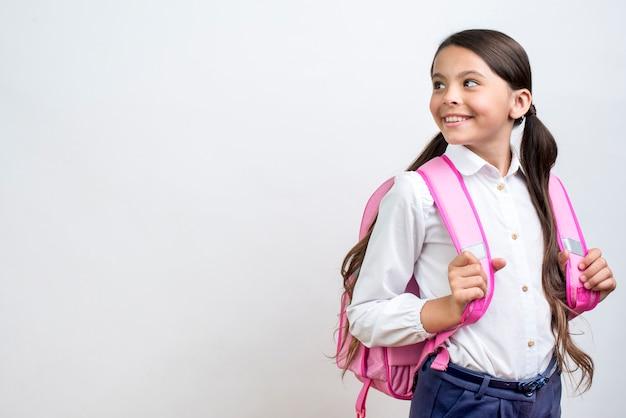 Inteligente colegiala hispana con mochila dando la vuelta. Foto Premium