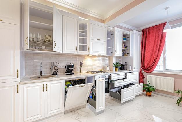 Interior de cocina blanca moderna de lujo con puertas y cajones abiertos Foto Premium