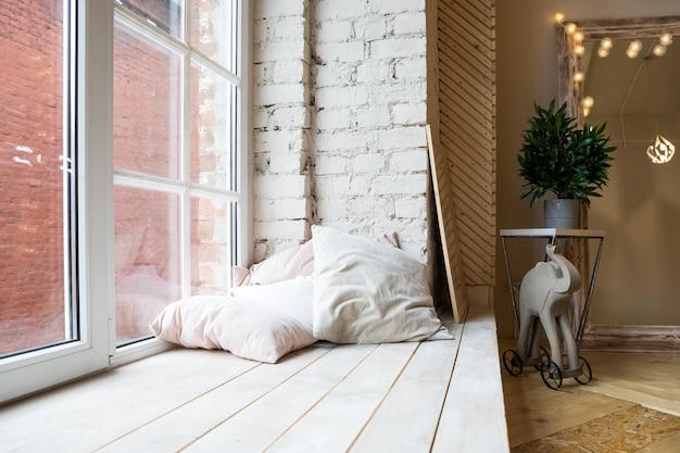 Interior con gran ventana, piso de madera. diseño de dormitorio estilo loft. Foto Premium