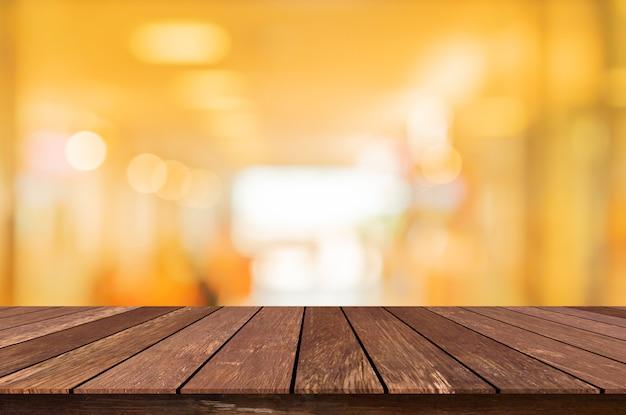 Interior moderno borrosa cafetería restaurante decorar con bombillas de luz de la lámpara en el techo y mesa de madera Foto Premium