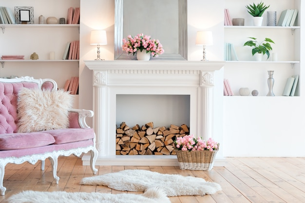 Interior moderno y luminoso con chimenea, flores de primavera y un acogedor sofá rosa. Foto Premium