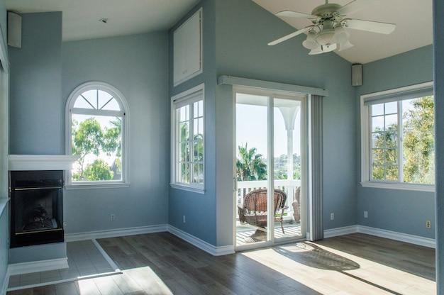 Interior moderno de moda de una sala de estar con paredes azules y ventanas blancas Foto gratis