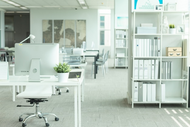 Interior de una oficina moderna con computadora y muebles blancos. Foto Premium