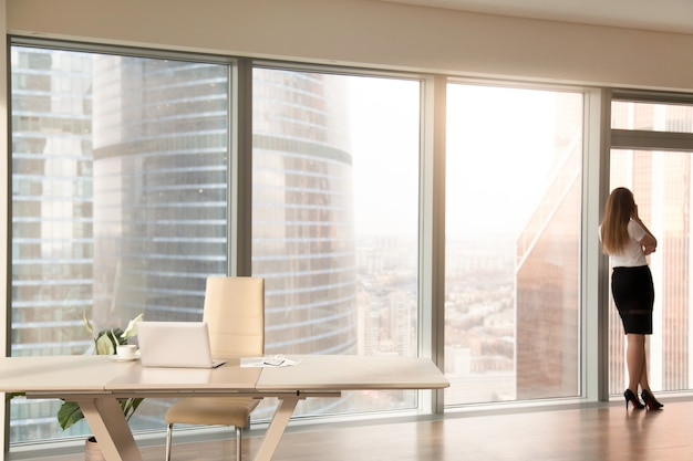 Interior de la oficina moderna con silueta femenina de pie en la ventana de cuerpo entero Foto gratis
