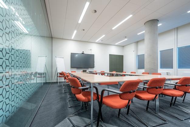 Interior de la sala de conferencias de una oficina moderna con paredes blancas y un monitor Foto gratis