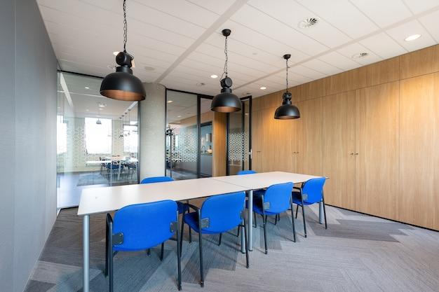 Interior de la sala de reuniones de una oficina moderna con una larga mesa de madera y sillas a su alrededor Foto gratis