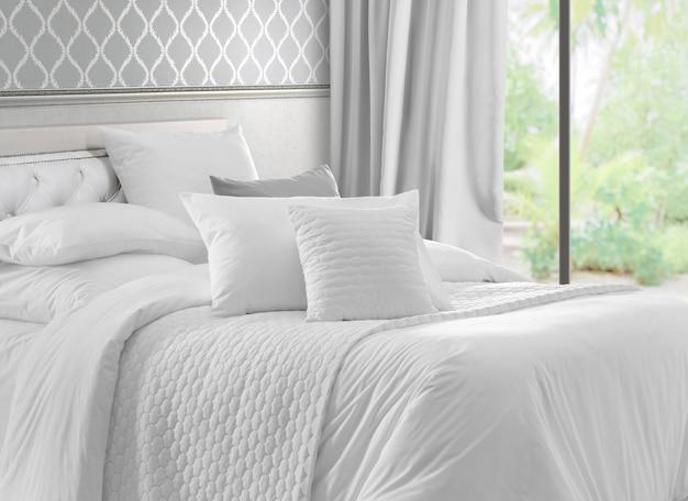 Interior con ventana vista jardín y cama blanca. Foto Premium