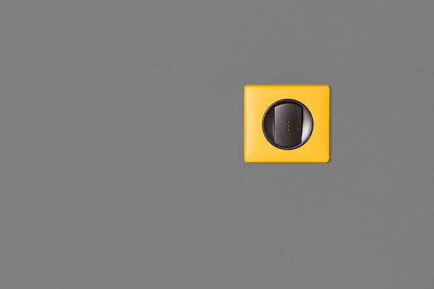 Interruptor de luz individual en pared gris. llaves de grafito y marco amarillo brillante. Foto Premium
