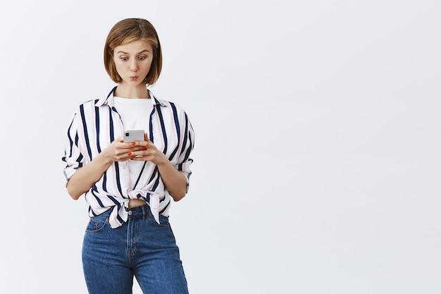 Intrigada y emocionada joven revisando mensajes o cuenta bancaria en el teléfono, mirando asombrado el teléfono inteligente Foto gratis
