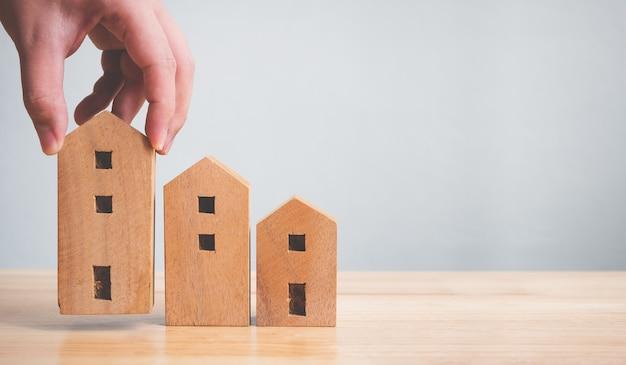 Inversión inmobiliaria de bienes raíces y concepto de hipotecas de vivienda. mano que sostiene la casa de madera en la mesa Foto Premium
