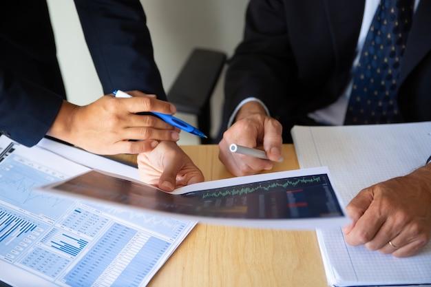 Inversor y corredor discutiendo la estrategia comercial, sosteniendo papeles con gráficos financieros y bolígrafos. toma recortada. concepto de inversión o trabajo de corredor Foto gratis