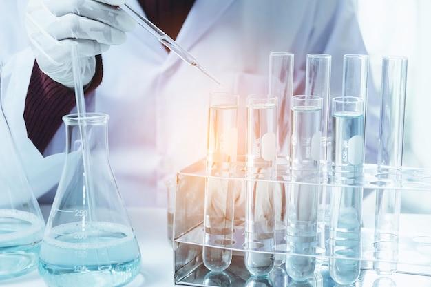 Investigador con laboratorio de vidrio de tubos de ensayo químicos con líquido para análisis Foto Premium