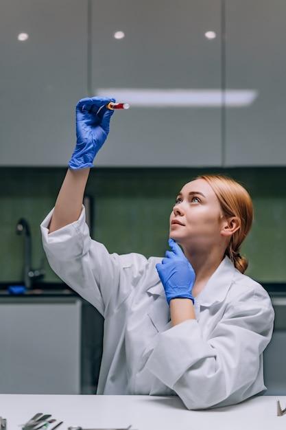 Investigador médico o científico femenino mirando un tubo de ensayo en un laboratorio. Foto gratis