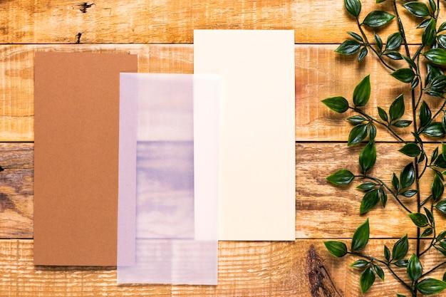 Invitación marrón en mesa de madera Foto gratis