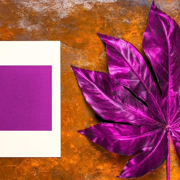 Invitación púrpura y hoja en la mesa Foto gratis