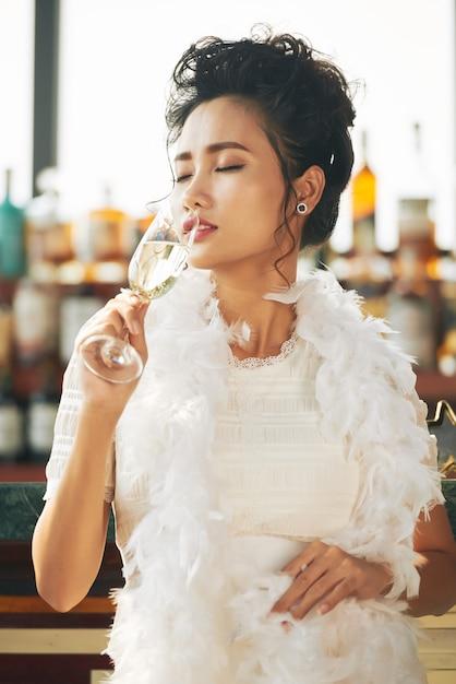 Invitada asiática disfrutando de copa de champán en la fiesta en el bar Foto gratis