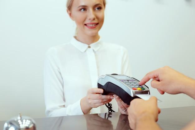 Invitado en la recepción del hotel pagando con cheque durante el check-in Foto Premium