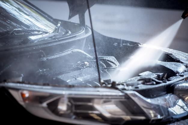 La inyección de lavar el motor mientras se lava el automóvil hace que el motor del motor brille y brille negro. Foto Premium