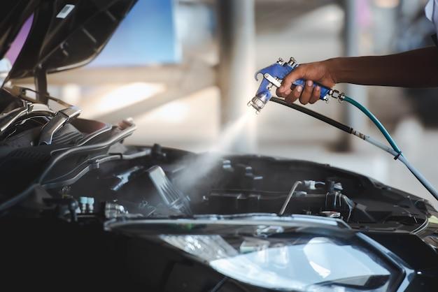 Inyecte la cera del motor después de lavar el automóvil para que el motor del automóvil brille y se vuelva negro. - encere el motor. Foto Premium
