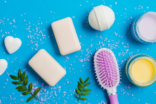 Jabón; bomba de baño crema hidratante y cepillo sobre fondo azul Foto gratis