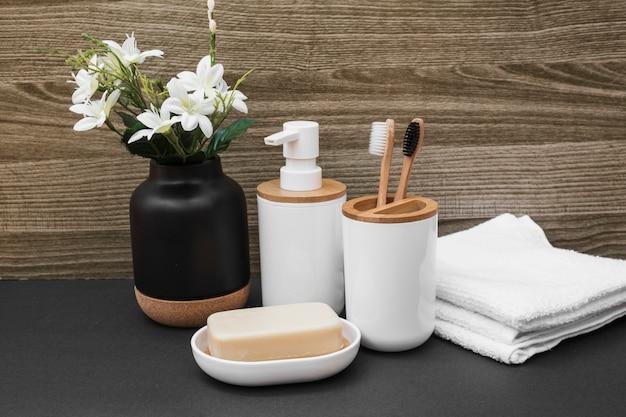 Jabón; cepillo de dientes; botella cosmética; toalla y florero blanco sobre superficie negra. Foto gratis