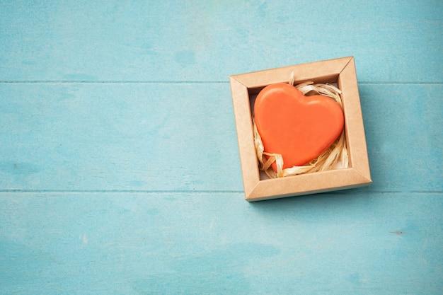 Jabón en forma de corazón en una caja de regalo sobre una superficie azul, Foto Premium