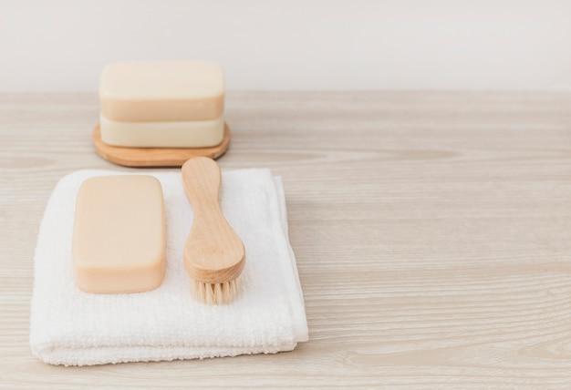 Jabón; pincel y toalla sobre tablero de madera Foto gratis