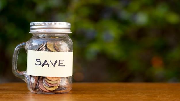 Jar con monedas y guardar la etiqueta al aire libre Foto gratis