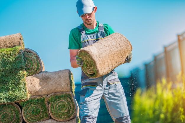 Jardinero con pedazo de césped Foto gratis