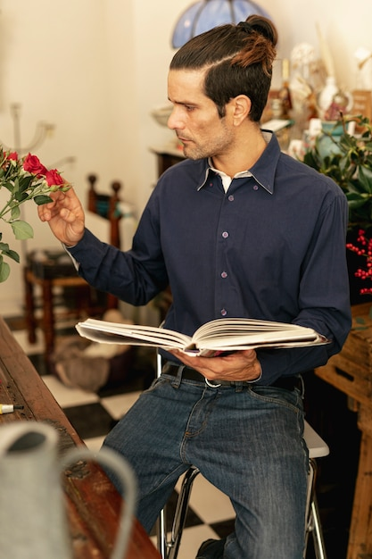 Jardinero sentado con un libro en sus manos. Foto gratis