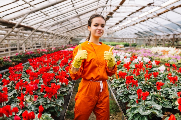 Jardinero de sexo femenino joven que gesticula los pulgares para arriba con las flores frescas que crecen en invernadero Foto gratis