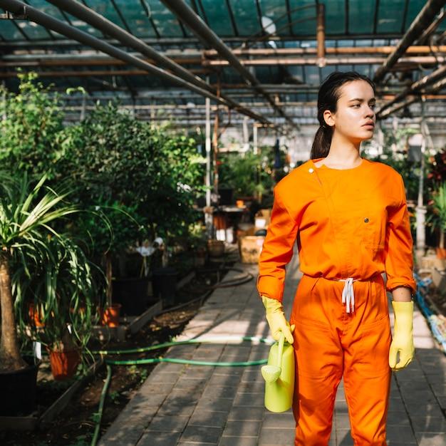 Jardinero de sexo femenino joven con la regadera que se coloca en invernadero Foto gratis