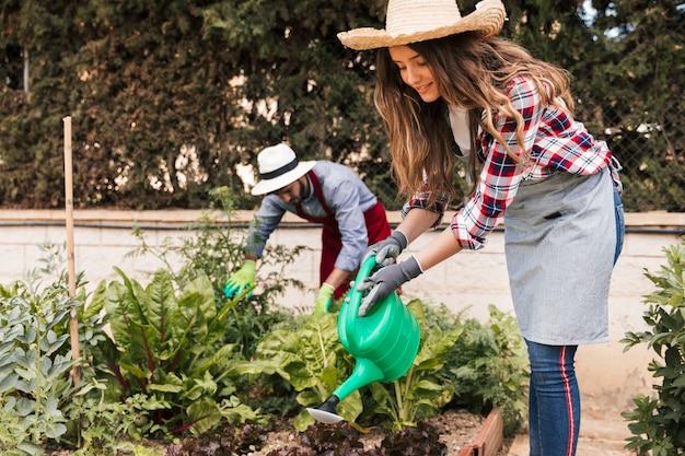 Jardinero de sexo masculino y de sexo femenino que trabaja en el jardín Foto gratis