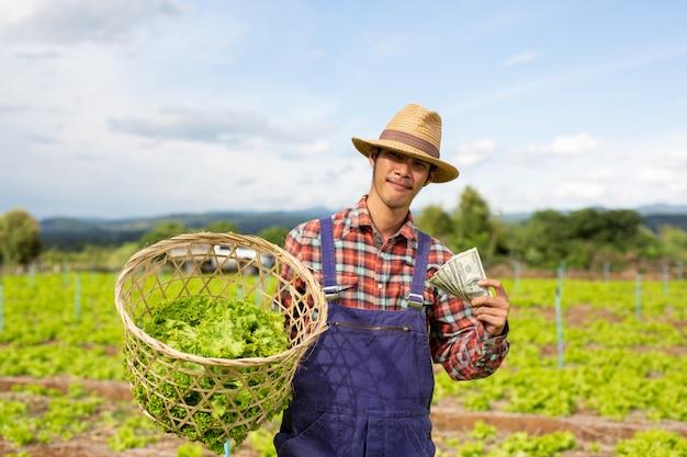 Jardineros varones que tienen verduras y moneda en dólares en sus manos. Foto gratis