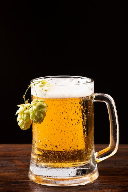 Jarra de cerveza con espuma y lúpulo sobre tabla de madera Foto gratis