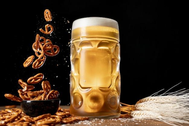 Jarra de cerveza con pretzels cayendo sobre una mesa Foto gratis